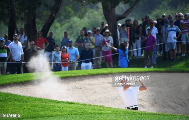 Haotong Li of China plays his second shot from a bunker on the 1st hole during the final round on day four of the Omega Dubai Desert Classic at...