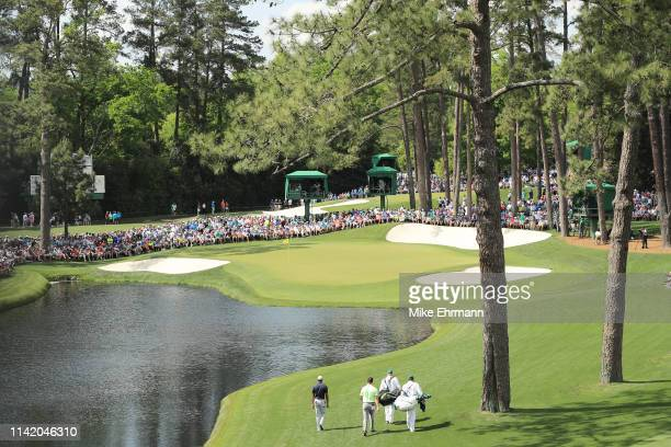 Haotong Li of China putts, Tiger Woods of the United States and Jon Rahm of Spain walk to the 16th green during the first round of the Masters at...