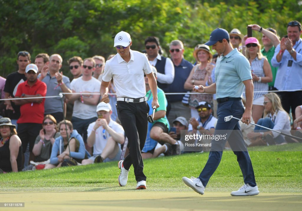 Haotong Li of China reacts after a birdie putt on the 15th green as Rory McIlroy of Northern Ireland looks on during the final round on day four of the Omega Dubai Desert Classic at Emirates Golf Club on January 28, 2018 in Dubai, United Arab Emirates.