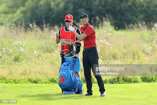 Haotong Li of China selects a club on the 14th hole during the first round of Made in Denmark at Himmerland Golf Spa Resort on August 25 2016 in...