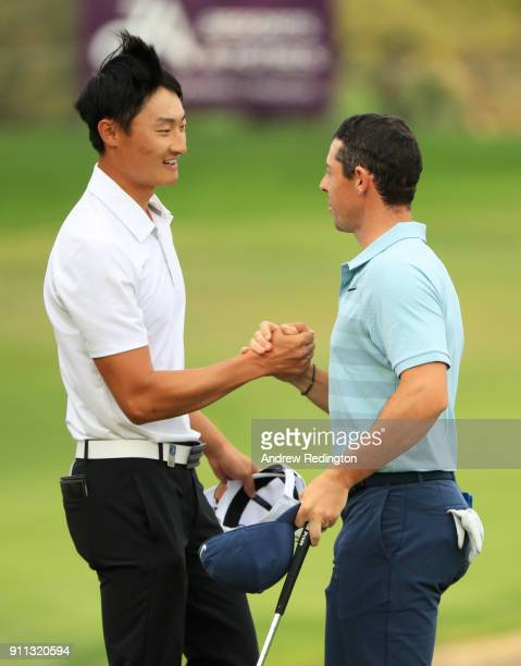 Haotong Li of China shakes hands with Rory McIlroy of Northern Ireland as he celebrates his victory during the final round on day four of the Omega...