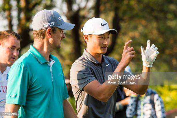 Haotong Li of China talks with Justin Rose of England during round one of the UBS Hong Kong Open at The Hong Kong Golf Club on November 23 2017 in...