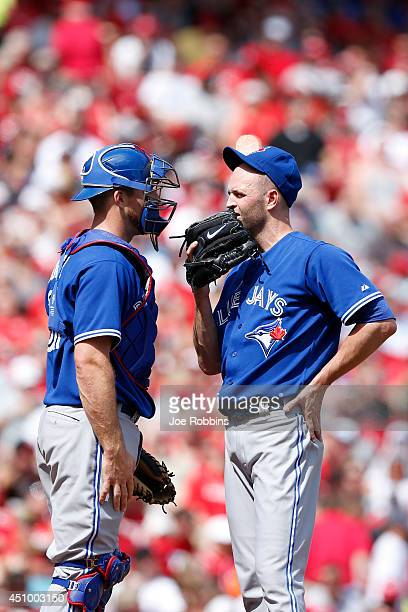 A Happ and Erik Kratz of the Toronto Blue Jays meet at the mound in the first inning of the game against the Cincinnati Reds at Great American Ball...