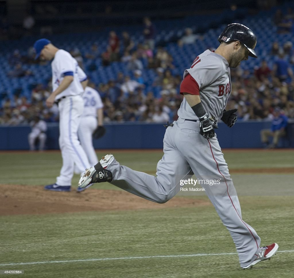 Happ looks down on the mound as Dustin Pedroia heads home after hitting a home run. Toronto Blue Jays Vs Boston Red Sox during MLB action at Rogers Centre on August 25, 2014.
