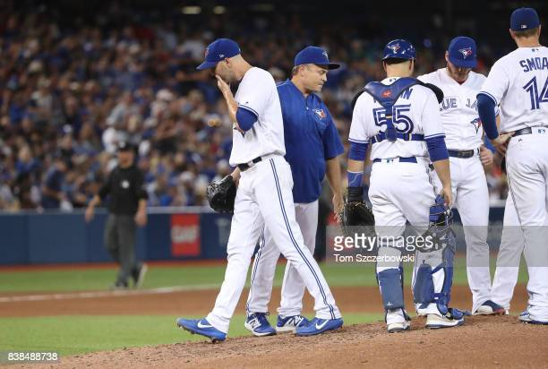 A Happ of the Toronto Blue Jays exits the game as he is relieved by manager John Gibbons in the sixth inning during MLB game action against the New...