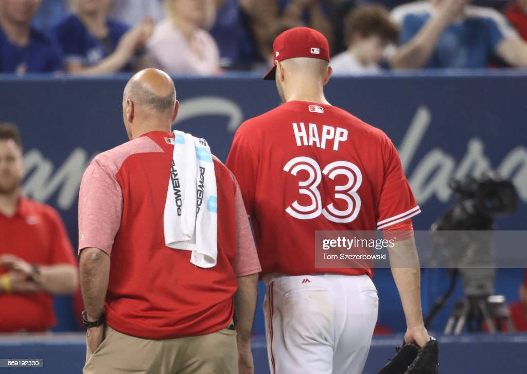 J.A. Happ #33 of the Toronto Blue Jays exits the game with trainer George Poulos due to an arm injury in the fifth inning during MLB game action against the Baltimore Orioles at Rogers Centre on April 16, 2017 in Toronto, Canada.