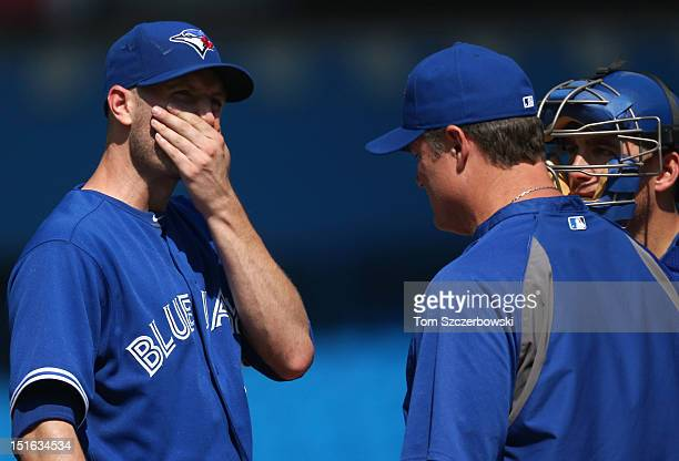 A Happ of the Toronto Blue Jays is relieved by manager John Farrell in the sixth inning as Jef Mathis looks on during MLB game action against the...
