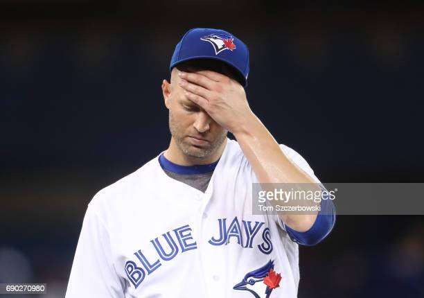 A Happ of the Toronto Blue Jays reacts after giving up a hit in the third inning during MLB game action against the Cincinnati Reds at Rogers Centre...