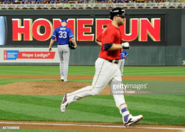 A Happ of the Toronto Blue Jays reacts as Brian Dozier of the Minnesota Twins rounds the bases after hitting a solo home run during the fifth inning...
