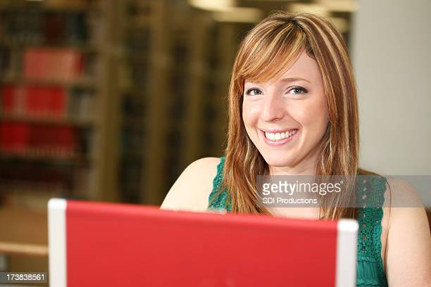 Happily Content Student Using Laptop at the Library