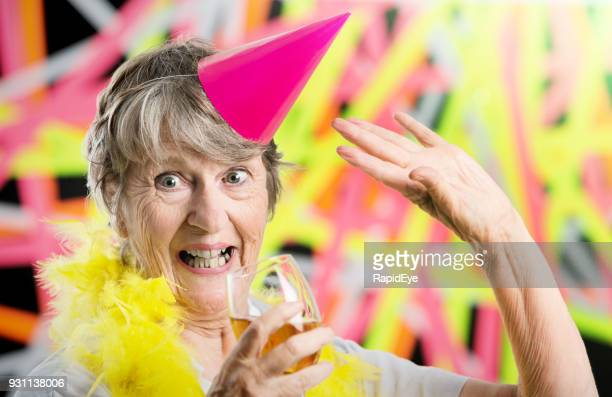 Happily excited old woman at party waves and smiles
