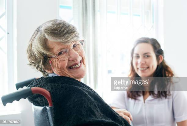 Happily smiling old lady with her friendly attendant