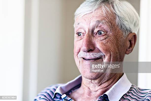Happily surprised old man smiles