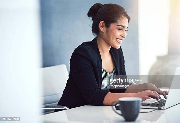 happily working away at her desk - typen stockfoto's en -beelden