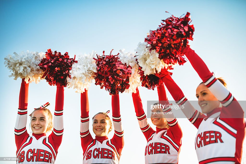 Happiness cheerleaders posing with pon-pon and arm raised : Stock Photo