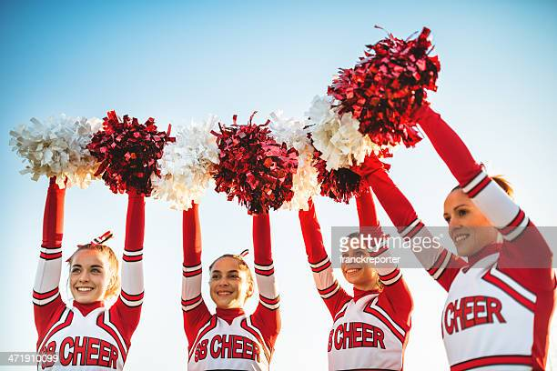 happiness cheerleaders posing with pon-pon and arm raised - cheerleaders stock photos and pictures