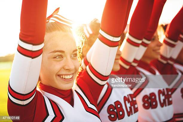 happiness cheerleaders posing with pon-pon and arm raised - teen cheerleader stock photos and pictures