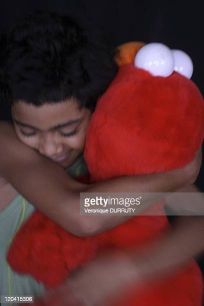 Happiness child giving a hug to an Elmo toy in France
