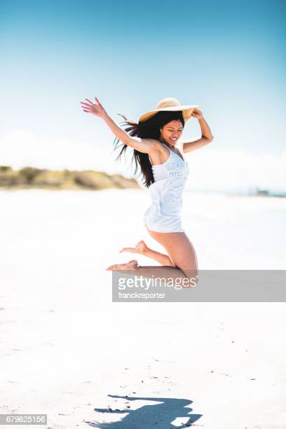happiness chinese woman jumping on the caribbean sea