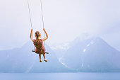 happiness concept, happy girl child on the swing on beautiful mountain landscape