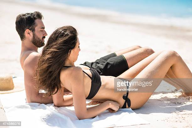 happiness couple at the seaside sunbathing - topless bikini models stock pictures, royalty-free photos & images