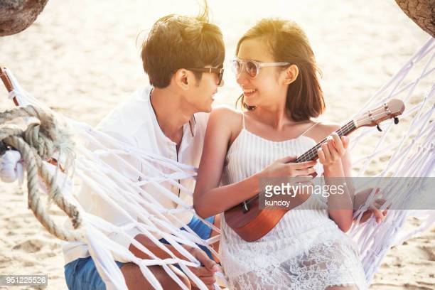 Happiness couple playing ukulele in summer times.