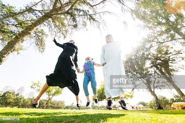 happiness family in dubai jumping in the park