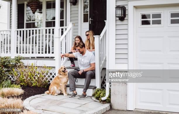 geluk familie met de hond in de voorkant van hun huis - voor stockfoto's en -beelden
