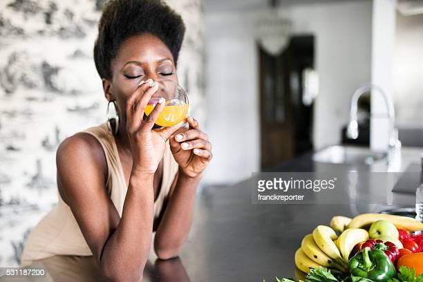 Glück-Frau trinken Saft aus der Orange