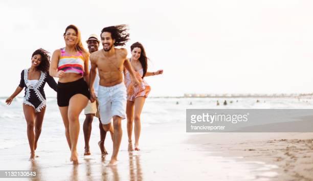 freund läuft glück am strand - dicke frauen am strand stock-fotos und bilder