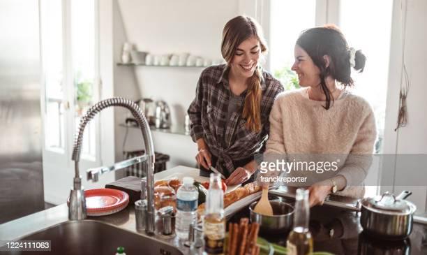 glücksfreunde kochen zu hause zusammen - weibliche freundschaft stock-fotos und bilder