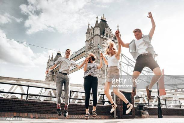 happiness friends in london at tower bridge jumping - london stock pictures, royalty-free photos & images