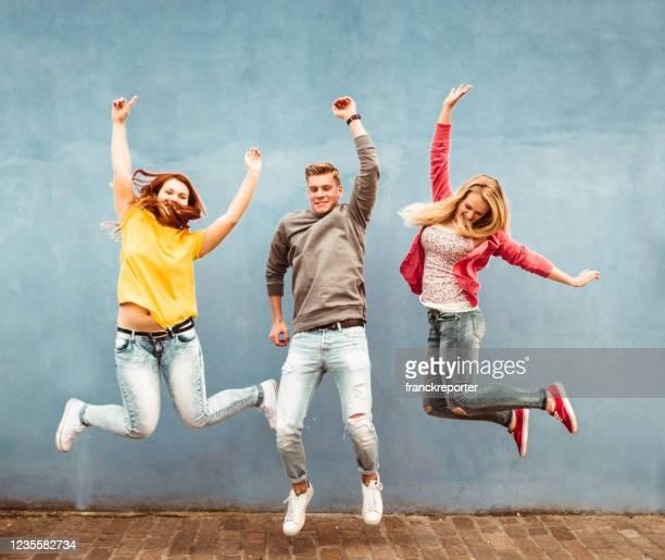 geluk vrienden springen samen - cheering stockfoto's en -beelden