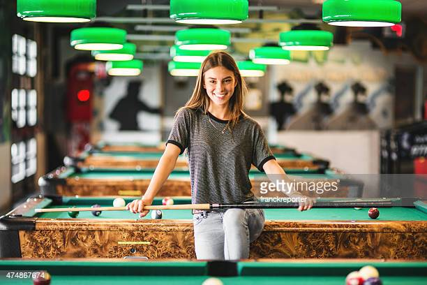 Happiness girl standing in a pub at the pool table