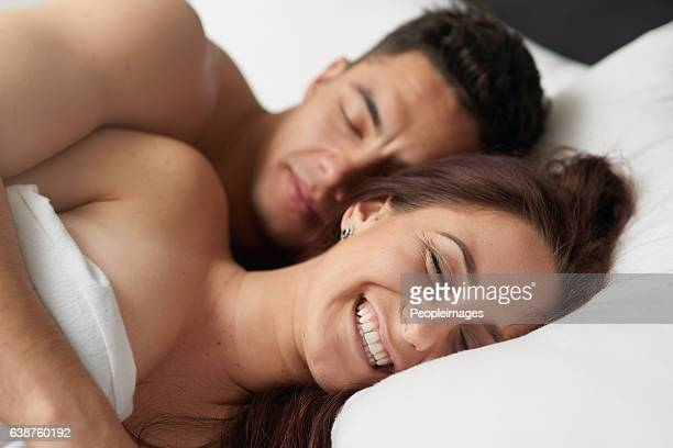 happiness is having someone to connect with - romantic young couple sleeping in bed stock photos and pictures