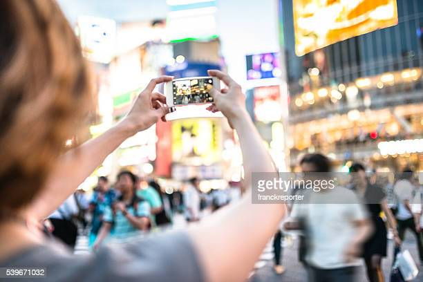 happiness japanese woman taking picture on shibuya - capturing an image stock pictures, royalty-free photos & images