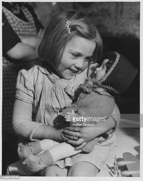 Happiness lights young Diana Burls face as she cradles her first Christmas present The threeyearold born in England during a World War II blitz is...