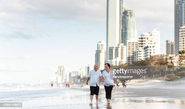 happiness senior couple running happiness in the city beach - gold coast queensland stock pictures, royalty-free photos & images