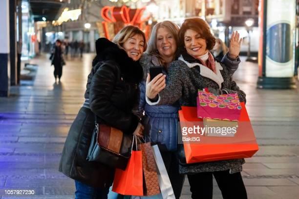 senior vrouwen geluk winkelen in de stad bij nacht - friday stockfoto's en -beelden