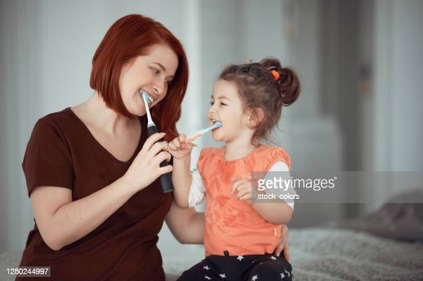 happiness starts in the morning with brushing our teeth - adulto de idade mediana imagens e fotografias de stock