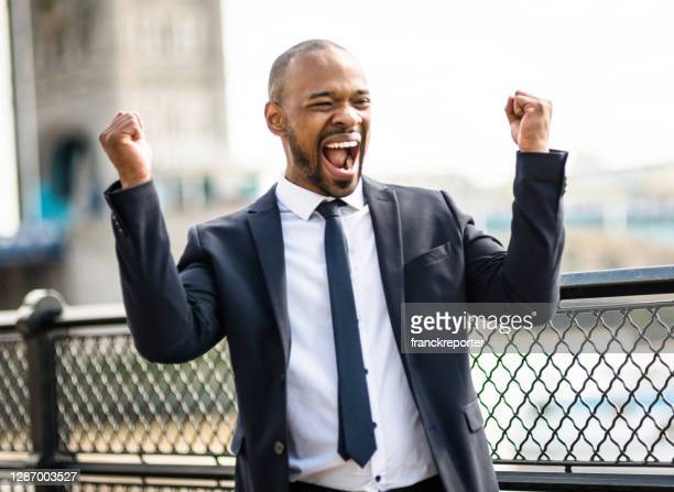 happiness winning businessman in london - fist stock pictures, royalty-free photos & images