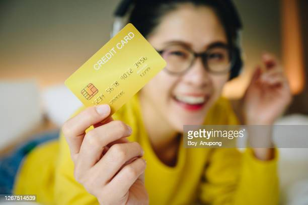 happiness woman holding a yellow credit card in her hand. - グリーティングカード ストックフォトと画像