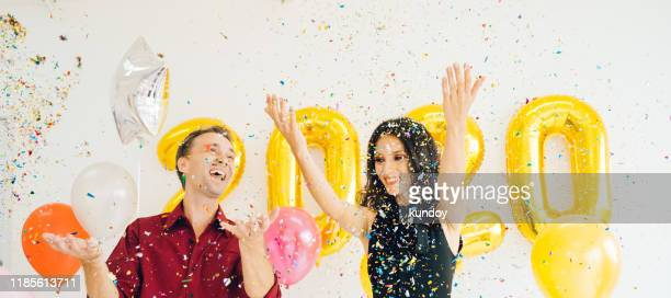 happiness young caucasian couple with party poppers in happy new year 2020 party. - クラッカー ストックフォトと画像