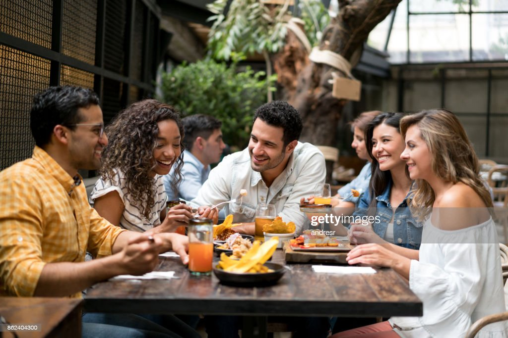 Happpy group of friends having dinner together at a restaurant : Stock Photo