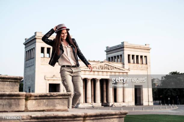 happpy young woman on stairs at koenigsplatz, munich, germany - munich stock pictures, royalty-free photos & images