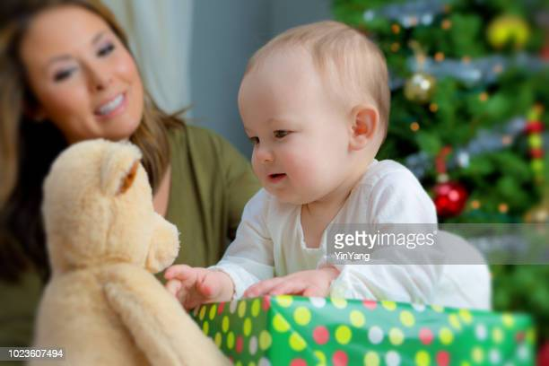 happy 10 months old baby and mother with christmas tree and gift - mama bear stock photos and pictures