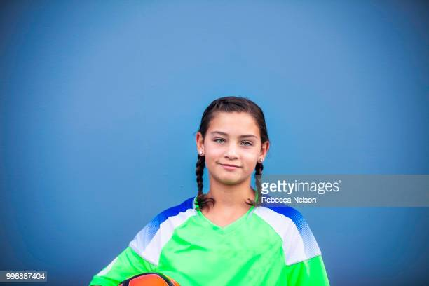 Happy 11 year old girl, wearing soccer jersey and holding soccer ball