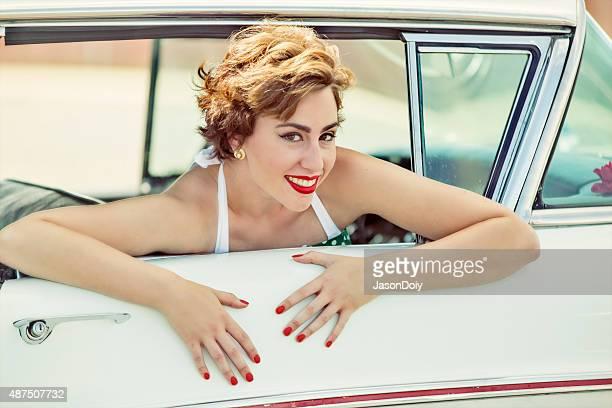 Glückliche 1950 er Frau Lächeln und Lauging in einem Oldtimer