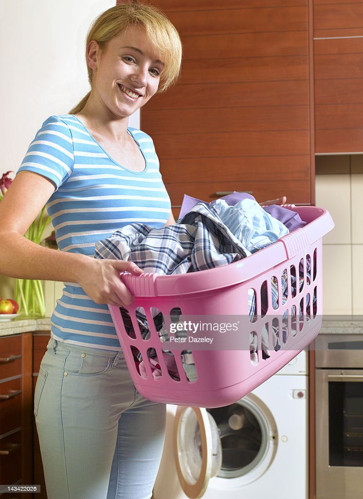 Happy 21 year old woman doing laundry : Stock Photo