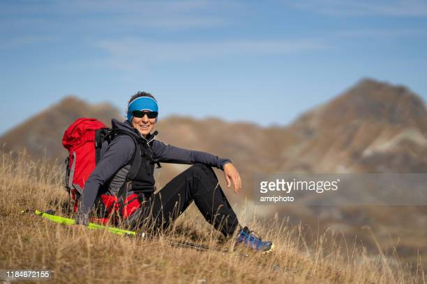 happy 45 years old hiking woman at short rest high up in mountains - 45 49 anni foto e immagini stock